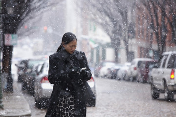 Asian woman walking in snow and checking cell phone