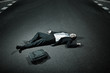 Asian businessman laying on asphalt roadway
