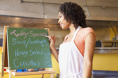 African American business owner writing cafe specials on blackboard