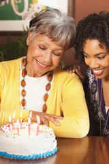 African American woman blowing out candles on birthday cake