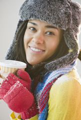 Mixed race woman in hat and gloves drinking coffee