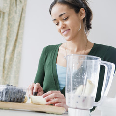 Mixed race woman preparing smoothie