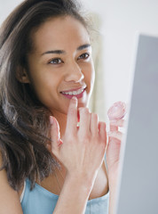Mixed race woman applying lip gloss
