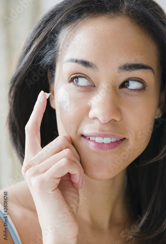 Mixed race woman applying lotion