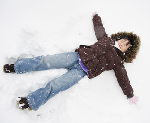 Chinese girl making snow angel