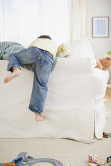 Black boy climbing over back of sofa