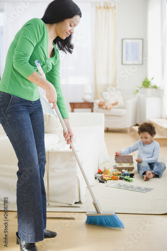 Mixed race mother sweeping floor
