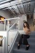 Ecuadorian businesswoman using laptop on staircase