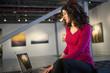 Ecuadorian businesswoman using laptop in art gallery
