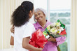 African American nurse giving senior woman flowers and gift