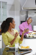 African American woman eating salad and talking on cell phone