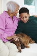 African American grandmother and grandson petting dog