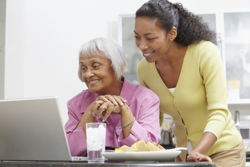 African American woman helping mother with laptop