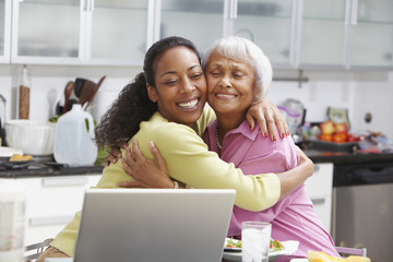 African American woman hugging mother in kitchen