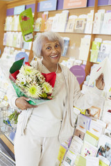 Senior African American woman buying flowers and greeting card
