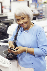 Senior African American woman text messaging on cell phone