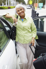 Senior African American woman standing with car and luggage