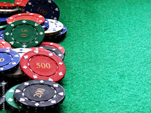 Poker chips on green felt background
