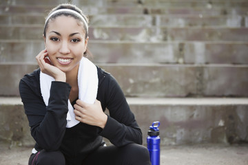 Mixed race woman sitting on steps with water bottle