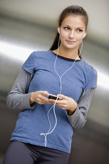Hispanic woman listening to music on mp3 player