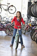 Mixed race girl choosing bicycle in shop