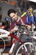 Hispanic man assembling bicycle in shop