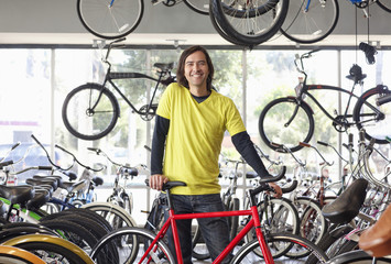 Mixed race bike shop owner standing with bicycle