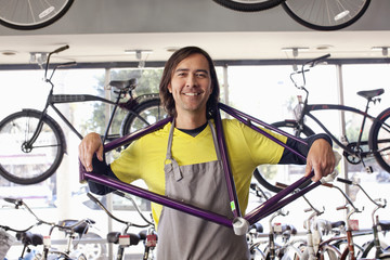 Mixed race bike shop owner holding bicycle frame