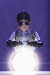 Korean boy in superhero costume looking at glowing orb