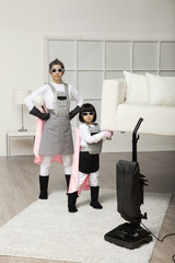 Korean superhero daughter lifting sofa for mother to vacuum underneath