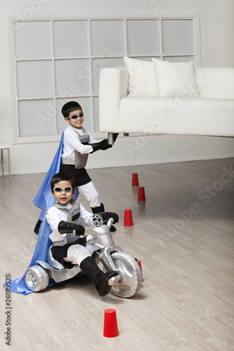 Korean superhero boy lifting sofa for brother to ride underneath