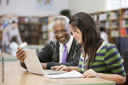 Librarian helping student do research in school library