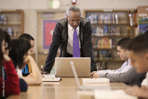 Librarian helping students in school library