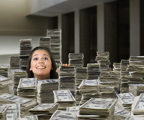 Mixed race woman surrounded by stacks of money