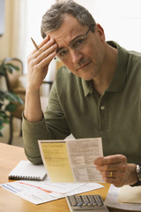 Caucasian man paying monthly bills