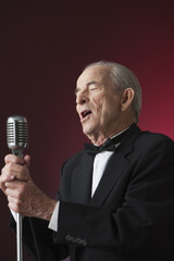 Senior Hispanic man singing into microphone