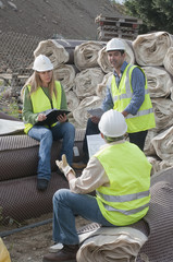 Hispanic construction workers having meeting outdoors