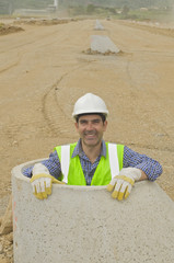 Hispanic construction worker standing in cement pipe