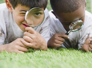 Boys looking at grass through magnifying glasses