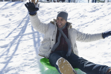 Mixed race man sledding on hill