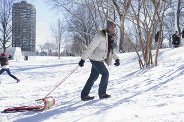 Mixed race man pulling sled uphill