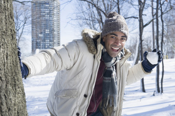 Mixed race man having snowball fight