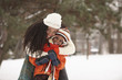 African American mother hugging daughter in snow
