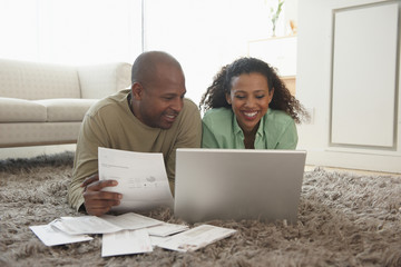 Couple in livingroom paying bills
