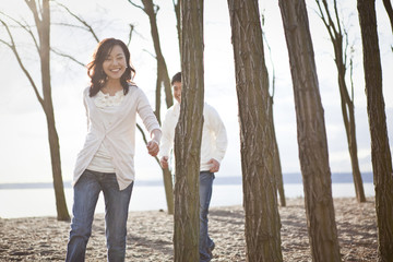 Korean couple walking on beach
