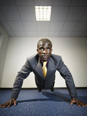 Black businessman doing push-ups