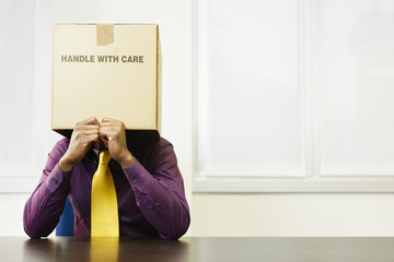 Black businessman with box over his head