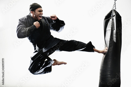 African American man karate kicking bag