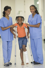 Nurses helping girl with broken leg to use crutches