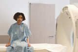 Mixed race patient in hospital gown waiting for MRI